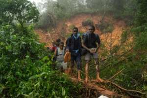 School students rescued by the Zimbabwean armed forces in Chimanimani walk past a mudslide caused by pounding rain. By ZINYANGE AUNTONY (AFP)