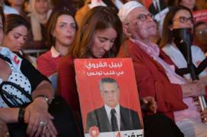 Salwa Smaoui, the wife of Tunisia's jailed presidential candidate Nabil Karoui, holds the media mogul's campaign poster at an event in Tunis.  By FETHI BELAID (AFP)
