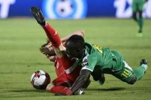 Senegalese Sadio Mane (R) and Tunisian Ayman Ben Mohamed fall as they contest possession.  By Khaled DESOUKI (AFP)