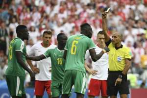 Senegal's Salif Sane (C) reacts as he receives a yellow card by referee Nawaf Abdullah Ghayyath Shukralla during their Russia 2018 World Cup Group H match against Poland, at the Spartak Stadium in Moscow, on June 19.  By FRANCK FIFE (AFP/File)