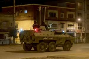 Security forces have deployed to stem the protests; here members of the National Guard patrol Ettadhamen on January 17.  By FETHI BELAID (AFP)