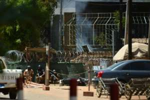 Security personnel take cover as smoke billows from the French Institute in Ouagadougou