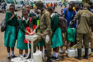 Secondary school students wash their hands at temporary hand washing point in Rwanda.  By STRINGER (AFP)
