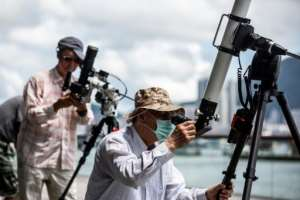 Skywatchers gathered on a Hong Kong waterfront to observe the spectacle.  By ISAAC LAWRENCE (AFP)