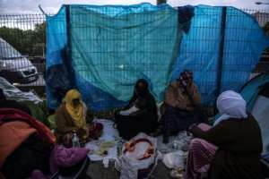Somalis having an evening meal at their camp at the Porte d'Aubervilliers. Local residents have complained about the acrid smoke of migrants' cooking fires.. By Christophe ARCHAMBAULT (AFP)