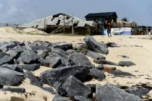 Some homes have been completely burrowed in sand at Alpha Beach.  By PIUS UTOMI EKPEI (AFP)