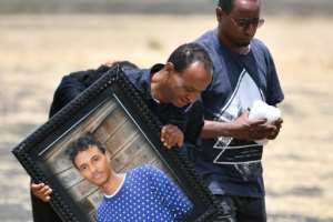 Some mourners carried pictures of their loved-ones. By TONY KARUMBA (AFP)