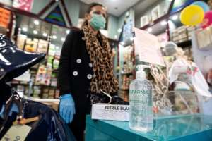 Some shops cautiously reopened in Italy, with clerks wearing face masks and gloves and offering hand sanitiser.  By Tiziana FABI (AFP)