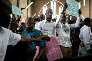 Some worshippers at Friday's mass held up protest banners