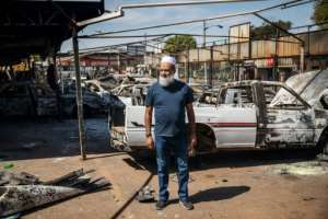 South African car dealership owner Yunus Salajee, outside the remains of the vehicles destroyed in the unrest.  By Michele Spatari (AFP)