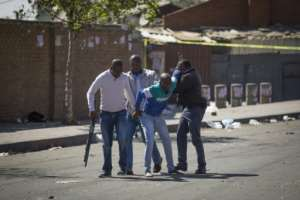South African police officers detained looters after the outbreak of rioting in the Johannesburg township of Alexandra.  By GUILLEM SARTORIO (AFP)