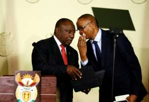 South African President Cyril Ramaphosa (L) listens to Director General in the Presidency Dr Cassius Lubisi after announcing the composition of the cabinet.  By Phill Magakoe (AFP/File)