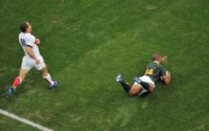 South Africa's winger JP Pietersen slides in to score as England's fly-half Andy Farrell looks on.  By RICHARD MARTIN (AFP/File)