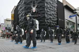 South Korean health officials from Bupyeong-gu Office wear protective gearto spray disinfectant at a shopping district in Incheon.  By Jung Yeon-je (AFP)