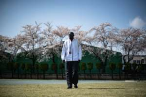 South Sudan coach Joseph Rensio Tobia Omirok supervises his athletes to a backdrop of cherry blossom as they train in Maebashi, north of Tokyo, where they were stranded after the Games were postponed.  By Philip FONG (AFP)