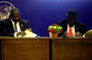 South Sudan President Salva Kiir (R) and rebel leader Riek Machar sign a power-sharing deal in Khartoum on August 5, 2018.  By ASHRAF SHAZLY (AFP)