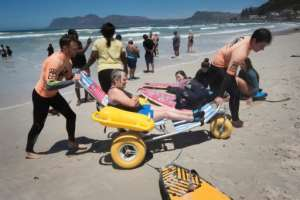 Smyth aims to increase the number of adaptive surfers -- not only showing people with disabilities that surfing is possible, but making it practically accessible to them. Here Alison Edwards, 54, is helped off the beach after a surf. By RODGER BOSCH (AFP)
