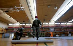 Spanish soldiers are setting up temporary shelters for homeless people in a country where more than 10,000 people have now died.  By JOSE JORDAN (STR/AFP)