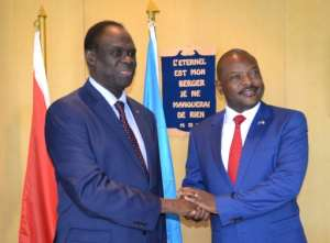 Special Envoy of The UN Secretary-General to Burundi Michel Kafondo, left, shakes hands with Burundi President Pierre Nkurunziza in Bujumbura on June 29, 2017.  By STR (AFP/File)