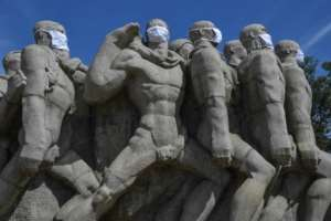 Statues of the Monumento das Bandeiras wear face masks in Sao Paulo, Brazil.  By NELSON ALMEIDA (AFP)