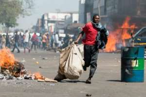 Street vendors flee with their goods as Zimbabwe opposition supporters clash with police in Harare