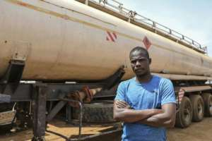 Stuck: Abderaman Hawara, 30, a truck driver from Chad, next to his rig.  By Daniel Beloumou Olomo (AFP)