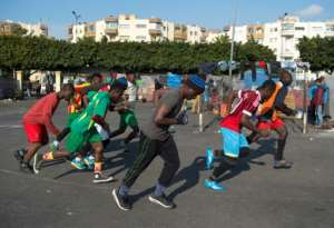 Sub-Saharan migrants train on a makeshift football pitch at the Oulad Ziane migrant camp in Casablanca on February 19, 2018