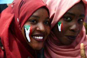 Sudanese women with national flags painted on their faces at a rally near military headquarters in the capital Khartoum. By ASHRAF SHAZLY (AFP)