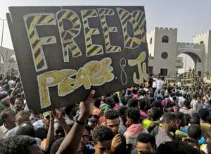 Sudanese anti-regime protesters outside the army headquarters in the capital Khartoum hold up a banner calling for