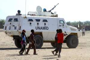 Sudanese children walk past an armoured vehicle of the United Nations and African Union peacekeeping mission (UNAMID) in Kalma Camp for internally displaced people in Nyala, the capital of South Darfur, on Wednesday.  By - (AFP)