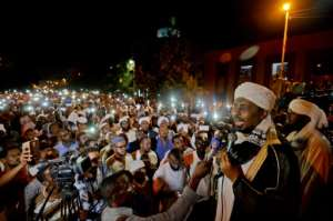 Sudanese hardline cleric Mohamed Ali Jazuli speaks as supporters of Islamist movements rally in front of the presidential palace on Saturday night.  By MOHAMED EL-SHAHED (AFP)
