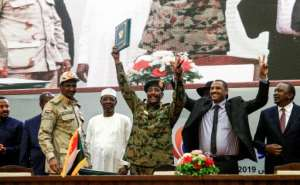 Sudanese protest leader Ahmad Rabie (2nd-R), flashes the victory gesture alongside General Abdel Fattah al-Burhan (C), head of the ruling military council, during a ceremony where they signed a