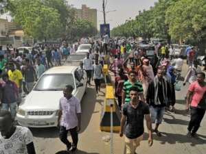 Sudanese protesters march towards the military headquarters as an army statement is awaited.  By - (AFP)