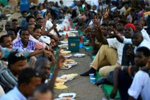 Sudanese protesters break their Ramadan fast outside the army headquarters in Khartoum on Tuesday. By Ashraf SHAZLY (AFP)