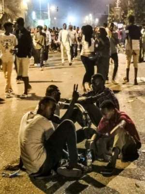 Sudanese protesters flash the victory gesture as they sit in the middle of a street in front of the military headquarters in the capital Khartoum. By - (AFP)