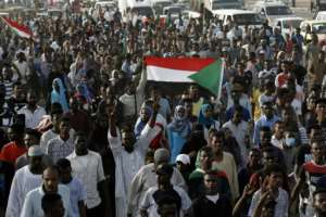 Sudanese protesters raise the national flag in the capital on Saturday.  By ASHRAF SHAZLY (AFP)