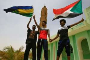Sudanese protesters, seen here waving the country's former and current national flags, have been locked in a months-long standoff with military generals who have resisted calls to hand power to civilians.  By ASHRAF SHAZLY (AFP)