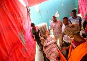 Sudanese protesters treat an injured man at a make-shift field hospital set up at the sit-in outside the army headquarters, after six people were shot dead overnight. By Mohamed el-Shahed (AFP)