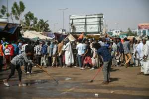 Sudanese protesters wait for tea and breakfast on Saturday as others sweep the street during the ongoing sit-in outside army headquarters in the capital.  By OZAN KOSE (AFP)