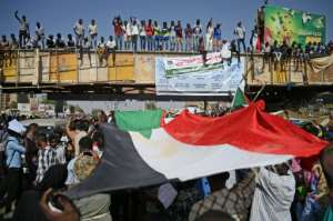 Sudanese protesters wave the national flag during a planned