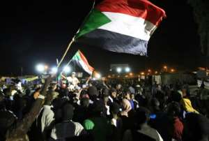 Sudanese protestors celebrate after the agreement was reached with the military council to form a three-year transition period for transferring power to a full civilian administration, in Khartoum, early on May 15, 2019. By ASHRAF SHAZLY (AFP)