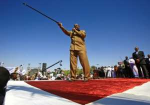 Sudanese President Omar al-Bashir brandished his trademark cane at a loyalist rally in Khartoum, the first in the capital since anti-government protests erupted last month.  By ASHRAF SHAZLY (AFP)