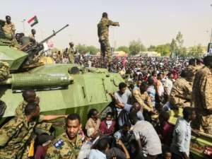 Sudanese soldiers stand on armoured vehicles as demonstrators continue their protest against the regime outside the army headquarters in Khartoum. By - (AFP)