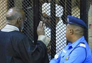 Sudan's deposed military president Omar al-Bashir sits in a defendant's cage during his corruption trial at a court in Khartoum on December 14, 2019.  By - (AFP/File)