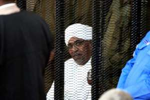 Sudan's deposed military ruler Omar al-Bashir sits in a defendant's cage during his corruption trial in Khartoum, pictured in August.  By Ebrahim HAMID (AFP/File)