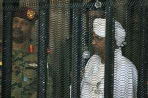 Sudan's deposed president Omar al-Bashir stands in a defendant's cage during the opening of his corruption trial in Khartoum last August.  By Ebrahim HAMID (AFP)