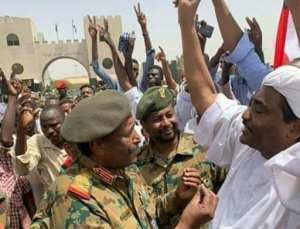 Sudan's second new military ruler in as many days, Lieutenant General Abdel Fattah al-Burhan, is seen talking with protesters before he assumed power outside army headquarters in a photograph released by state news agency SUNA.  By - (SUDAN NEWS AGENCY/AFP)
