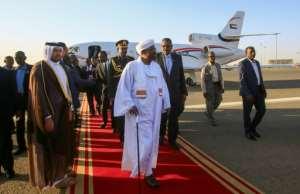 Sudan's President Omar al-Bashir (C) is received upon his return from Qatar at Khartoum international airport.  By ASHRAF SHAZLY (AFP)