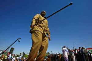 Sudan's President Omar al-Bashir waves his trademark cane in defiance as he tells thousands of supporters at a loyalist rally in Khartoum on January 9, 2019 that his government will not give in to economic pressure.  By ASHRAF SHAZLY (AFP)