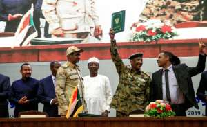 Sudan's protest leader Ahmad Rabie (R), flashes the victory gesture alongside General Abdel Fattah al-Burhan (L), the chief of Sudan's ruling Transitional Military Council after signing the landmark